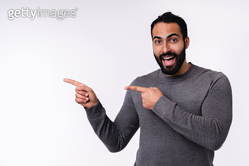 Excited young arabian man in casual clothes pointing at copy space isolated over white background