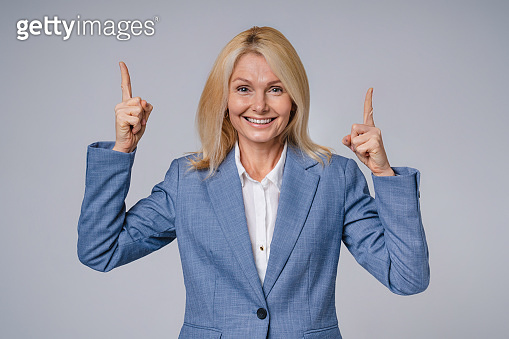 Excited senior business woman pointing at copy space in formal attire isolated over grey background