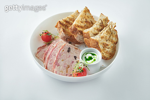 A classic French dish - terrine with chicken, ham and vegetables in a white plate with rye croutons. White background