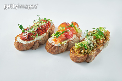 Italian appetizer - three bruschetta with tomatoes, salmon and baked peppers on a white background