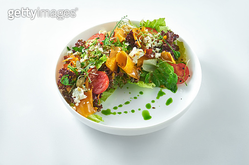 Appetizing and dietetic salad of roasted pumpkin, arugula, feta and tomatoes in the white plate on a white background.