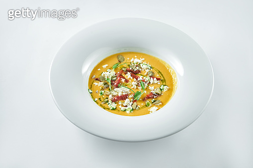 Appetizing pumpkin cream soup with feta, sun-dried tomatoes and microgreen on a white background in a white plate