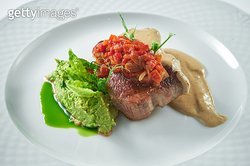 Appetizing pork steak with tomato salsa, mushroom sauce and mashed peas in a white plate. Close up, selective focus