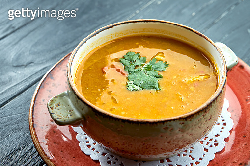 Traditional Moroccan soup - Harira, yellow lentil soup with cilantro in a red plate on a black wood background. Diet soup