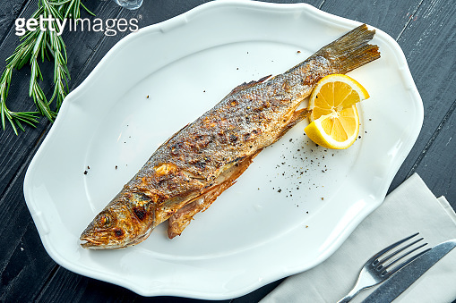 Whole grilled trout on charcoal fire, served in a white plate with lemon on a dark wood background.