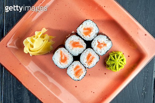 Appetizing Japanese sushi - maki with salmon served in a plate with ginger and wasabi on a black wood background. Japanese cuisine