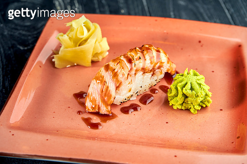 Appetizing Japanese nigiri with smoked salmon and unagi sauce, served in a plate with ginger and wasabi on a black wooden background