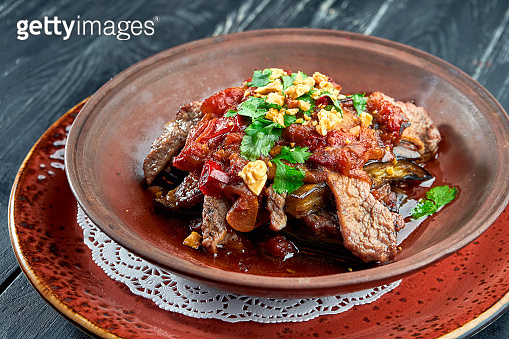 Baked beef with eggplant, nuts, tomatoes and cilantro in clay, served in a bowl on a black background. Restaurant food.