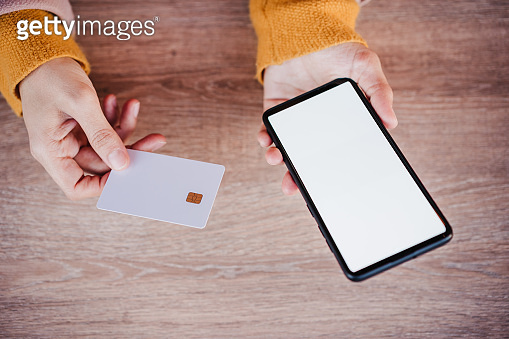 unrecognizable happy caucasian woman in terrace using mobile phone device and credit card for online shopping. Technology and lifestyle concept