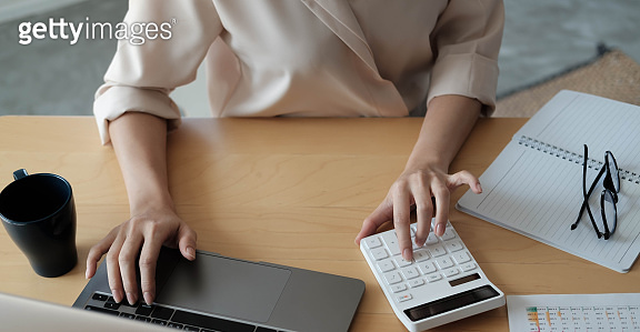 Close up Businesswoman using calculator and laptop for do math finance on wooden desk in office and business working background, tax, accounting, statistics and analytic research concept