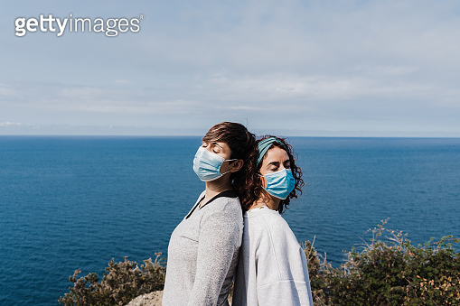 two caucasian women outdoors wearing face mask keeping social distance in Pandemic during corona virus. Nature and mountain