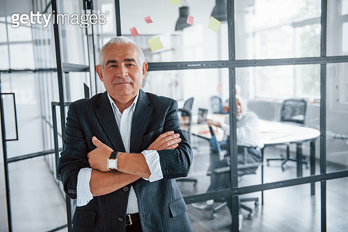 Portrait of senior man that stands in front of aged team of elderly businessman architects that have a meeting in the office