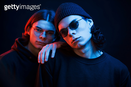 Leaning on the brother. Portrait of twins. Studio shot in dark studio with neon light