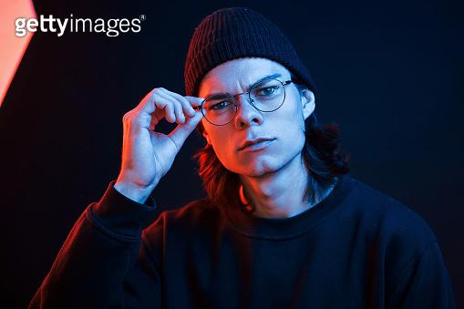 Confident look. Studio shot in dark studio with neon light. Portrait of serious man