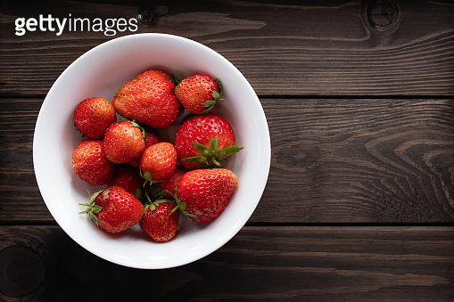 Natural ripe strawberries in a plain white bowl on a dark wooden background. Top view, copy space