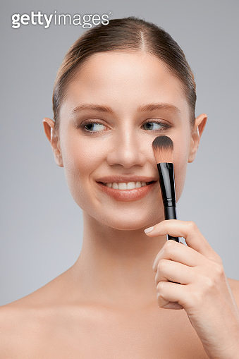 Gorgeous young lady holding makeup brush and posing in studio. Beauty photography