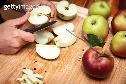Organic apples are cutting in chunks, preparation for baking a pie or cooking a applesauce