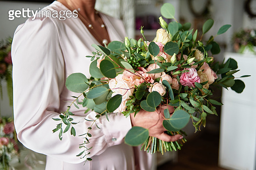 Luxury bridal bouquet of pink and beige roses and eucalyptus in bride's hands, copy space. Wedding, birthday, holidays concept