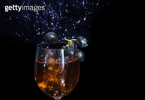A glass of grape wine close-up, on a black background. Splashes of wine