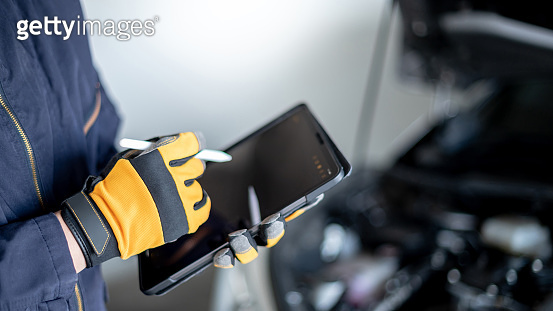 Auto mechanic hand using digital tablet for checking car
