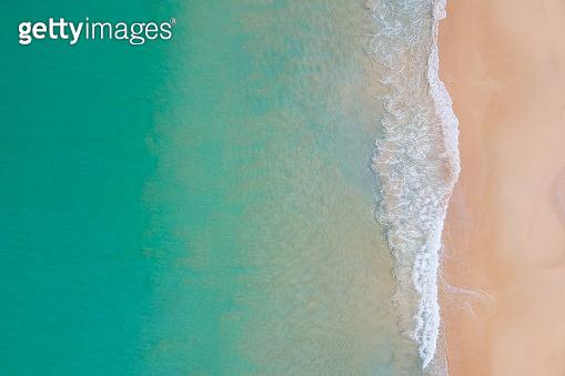 Aerial view of ocean wave reaching the coastline