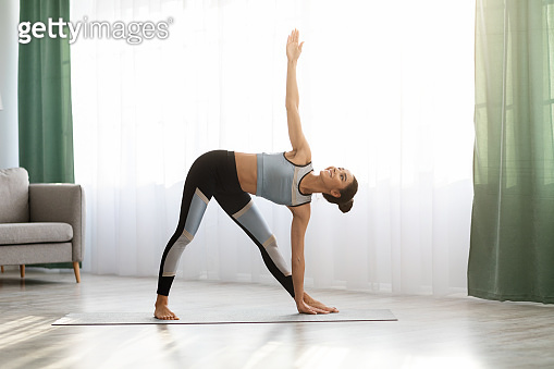 Slim sporty lady practicing yoga at home