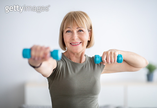 Portrait of positive senior lady exercising with dumbbells at home during covid-19 quarantine
