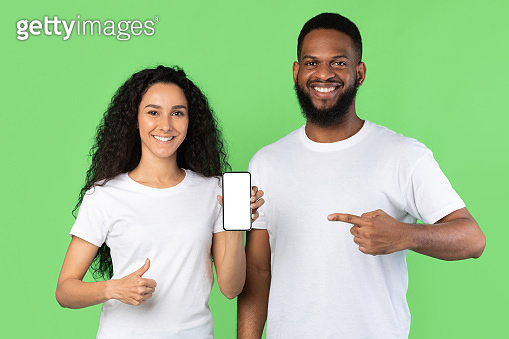 Couple Showing Phone Empty Screen Gesturing Thumbs-Up Over Green Background