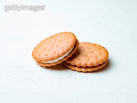 Two round sandwich cookies on white background.