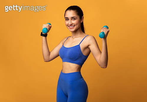 Smiling Sporty Woman Posing With Dumbbells Isolated On Orange Background