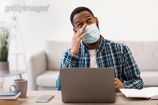 Black Man Touching Eyes Wearing Face Mask Sitting In Office