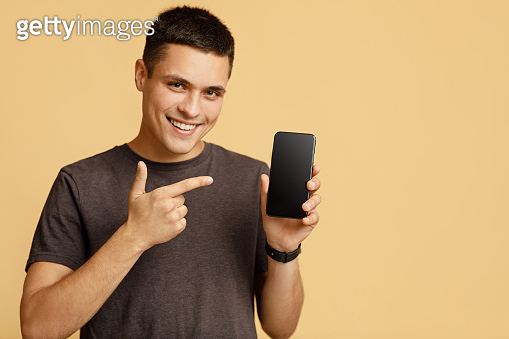 Excited winner man demonstrating mobile phone after received good news