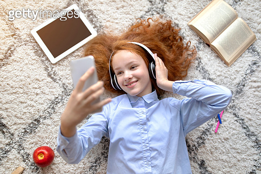 Girl wearing headphones enjoying music with smartphone