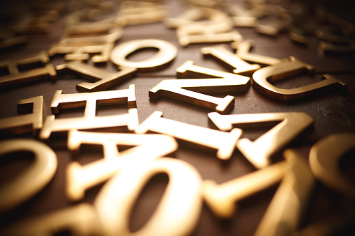 Golden metal letters on wood