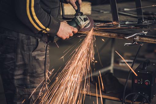 repairman grinding metal