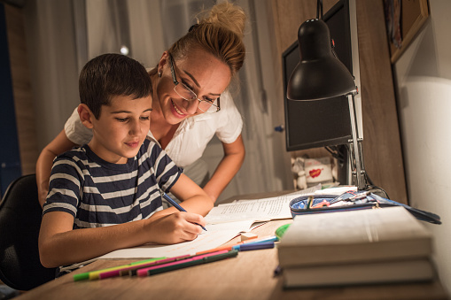 Boy doing homework with mother