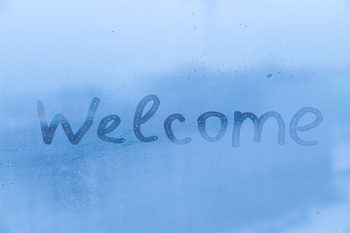 The child inscription welcome on the blue evening or morning window glass with drops