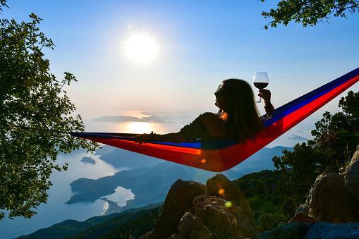 Woman drinking wine in hammock