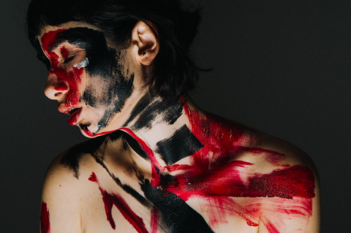 Model's face and body covered with paint