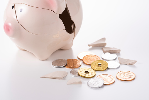 Cracked piggy and coins on white background