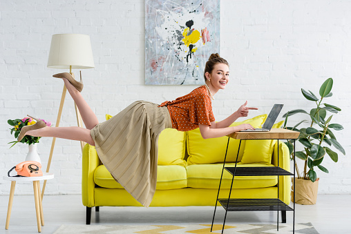 elegant young woman levitating in air and pointing with finger at laptop