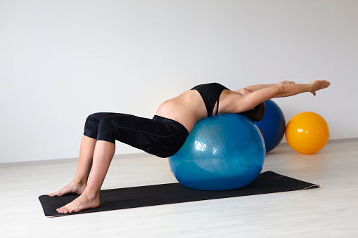 Young pregnant woman doing fitness exercises