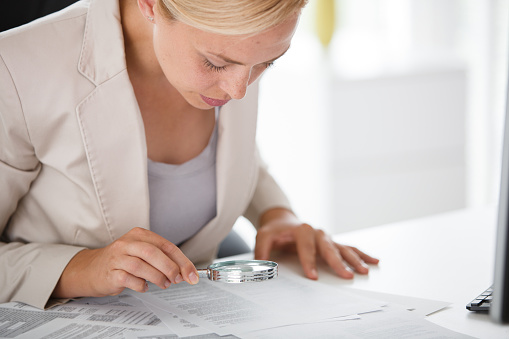 Businesswoman using magnifying glass while reading legal documents