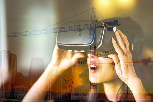 Young woman looking with VR behind the glass reflection of city view and construction site on window, double exposure