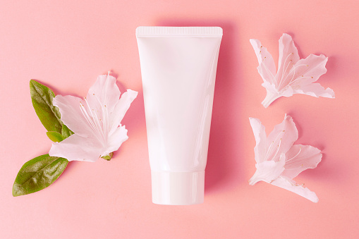 Tube with cream on pink background, top view, natural cosmetics concept