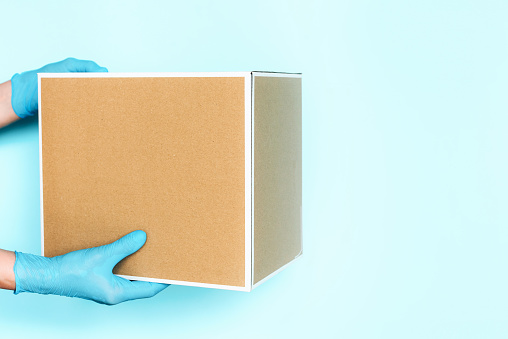 Hand in medical glove gives craft box over blue background. Contactless online shopping concept. Banner, copy space. Fast and free delivery transport . Online shopping and Express delivery