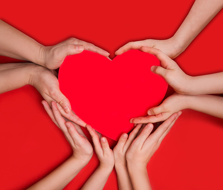 Group of people hands of adults and children holding a red heart icon against a red background