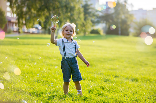 Cute preschool blond child, playing in the park on sunset, summertime