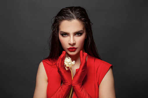 Lady in red evening dress with white flowers. Stylish woman in red gloves, fashion model on black portrait