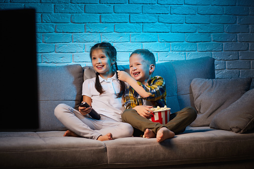 two children with remote control watching TV